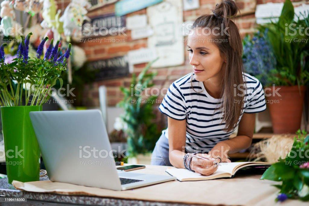 Jeune fleuriste écrivant dans le cahier et regardant l'ordinateur portatif tout en se penchant sur le compteur - Photo de Adulte libre de droits