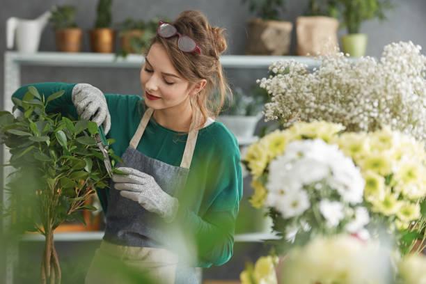 young flower shop owner - fleuriste photos et images de collection