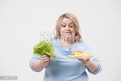 istock Young fluffy fat woman in casual blue clothes on a white background holding green salad leaves and a plate of fast food, hamburger and fries. Diet and proper nutrition. 1132777971