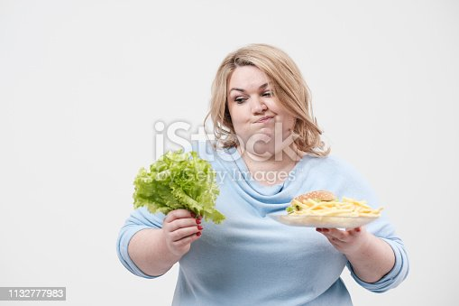 1132777983 istock photo Young fluffy fat woman in casual blue clothes on a white background holding green salad leaves and a plate of fast food, hamburger and fries. Diet and proper nutrition. 1132777983