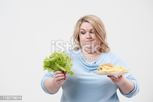 1132777983 istock photo Young fluffy fat woman in casual blue clothes on a white background holding green salad leaves and a plate of fast food, hamburger and fries. Diet and proper nutrition. 1132778014