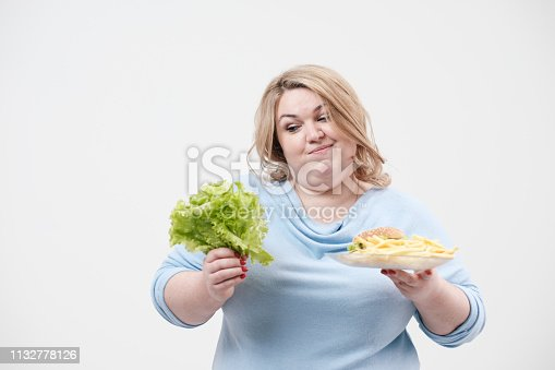 1132777983 istock photo Young fluffy fat woman in casual blue clothes on a white background holding green salad leaves and a plate of fast food, hamburger and fries. Diet and proper nutrition. 1132778126