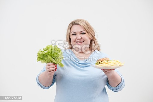 1132777983 istock photo Young fluffy fat woman in casual blue clothes on a white background holding green salad leaves and a plate of fast food, hamburger and fries. Diet and proper nutrition. 1132778648