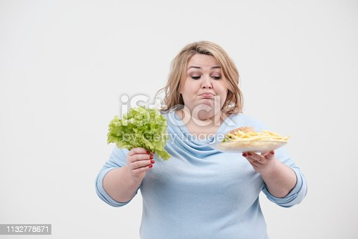1132777983 istock photo Young fluffy fat woman in casual blue clothes on a white background holding green salad leaves and a plate of fast food, hamburger and fries. Diet and proper nutrition. 1132778671