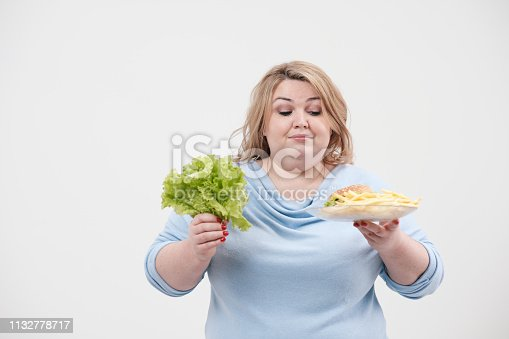 1132777983 istock photo Young fluffy fat woman in casual blue clothes on a white background holding green salad leaves and a plate of fast food, hamburger and fries. Diet and proper nutrition. 1132778717