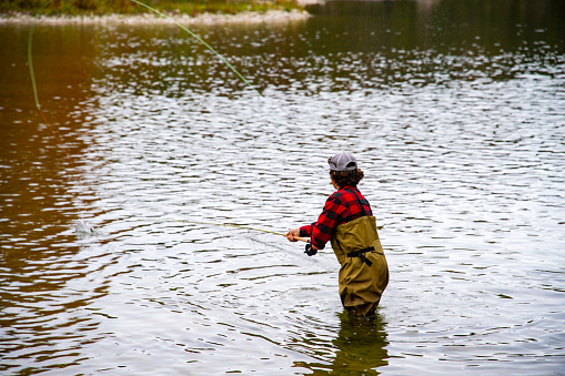 Fly-fishing on a beautiful Autumn day. A young fly fisherman in a river during the fall.