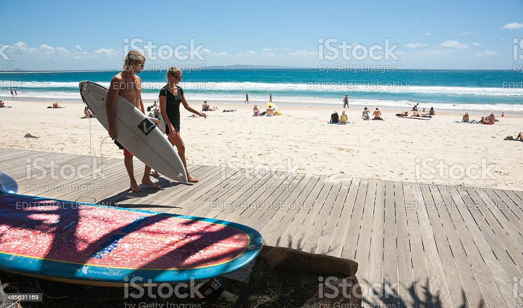 Young folk carrying surfboard, walking and talking, Noosa, Queensland, Australia. stock photo