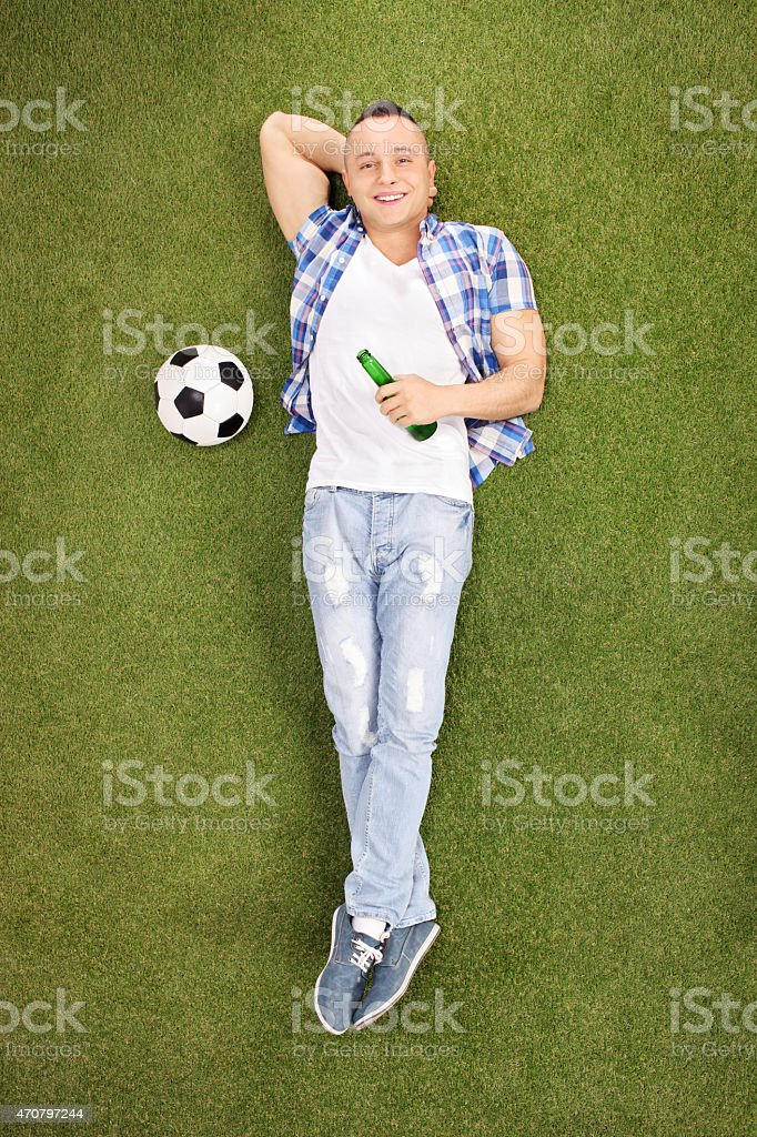 Young football fan lying on grass and drinking beer stock photo