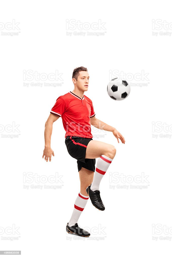 Young football player juggling a ball stock photo