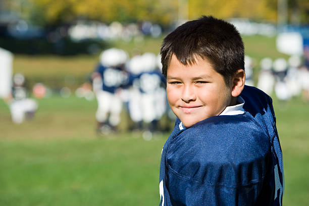 Young football player Young football player on the sidelines.  Football game in the background. line of scrimmage stock pictures, royalty-free photos & images