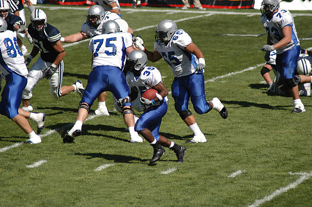 Young football player rushing for a touchdown Number 35 sprints for the touchdown with great support from his blockers.  No copyrighted or trademarked content in this shot. wide receiver athlete stock pictures, royalty-free photos & images