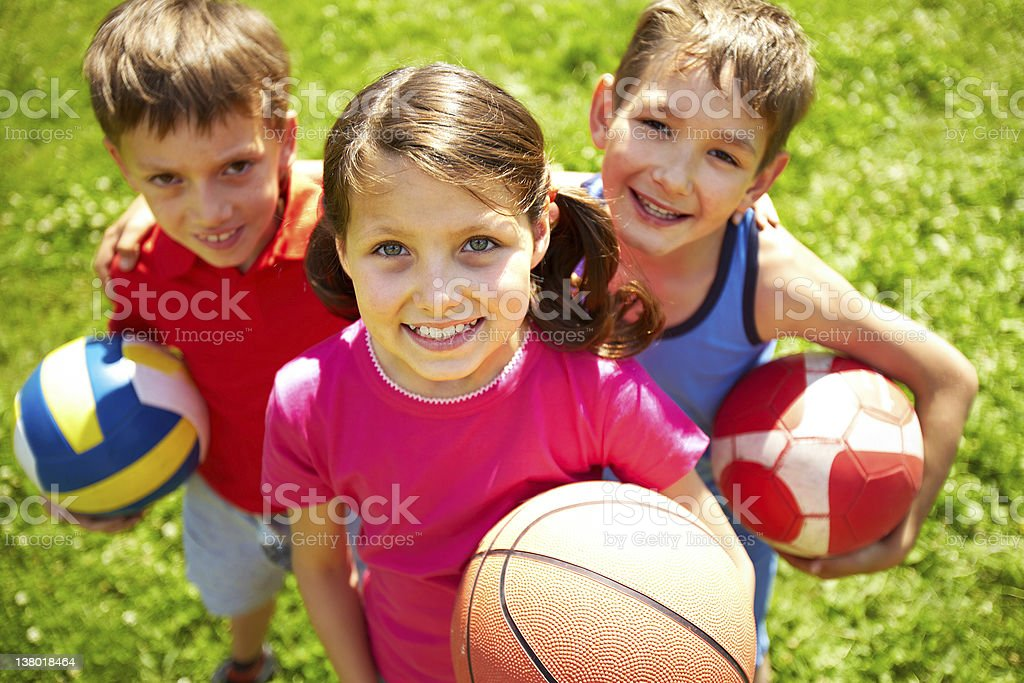 Portrait of three little children with balls looking at camera and...