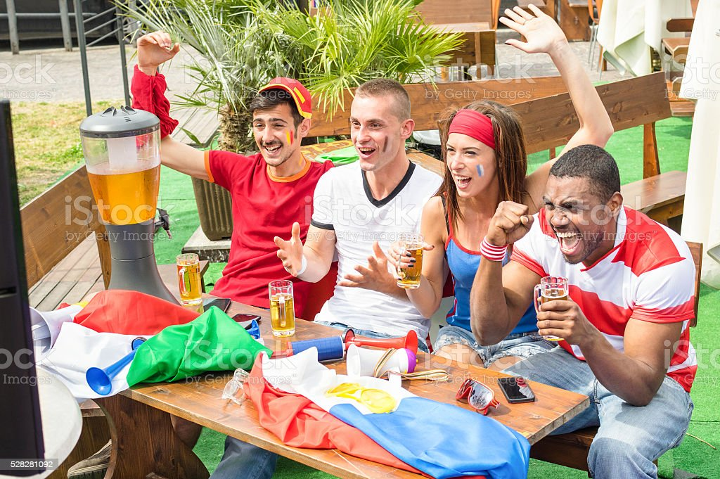 Young football supporter fans cheering with beer watching sport match stock photo