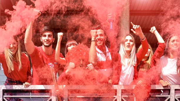 jonge voetbal supporter fans juichen met gekleurde rook kijken soccer match samen op stadion - vrienden groep mensen met rode t-shirts hebben opgewonden plezier op sport wereld kampioenschap concept - internationale voetbal stockfoto's en -beelden