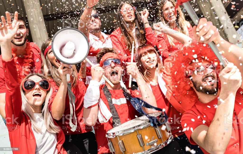 Jóvenes fanáticos supporter animando con bandera y confeti viendo fútbol partido en el estadio - grupo de amigos de personas con camisetas rojas que excitó la diversión en concepto de Campeonato del mundo de deporte - foto de stock