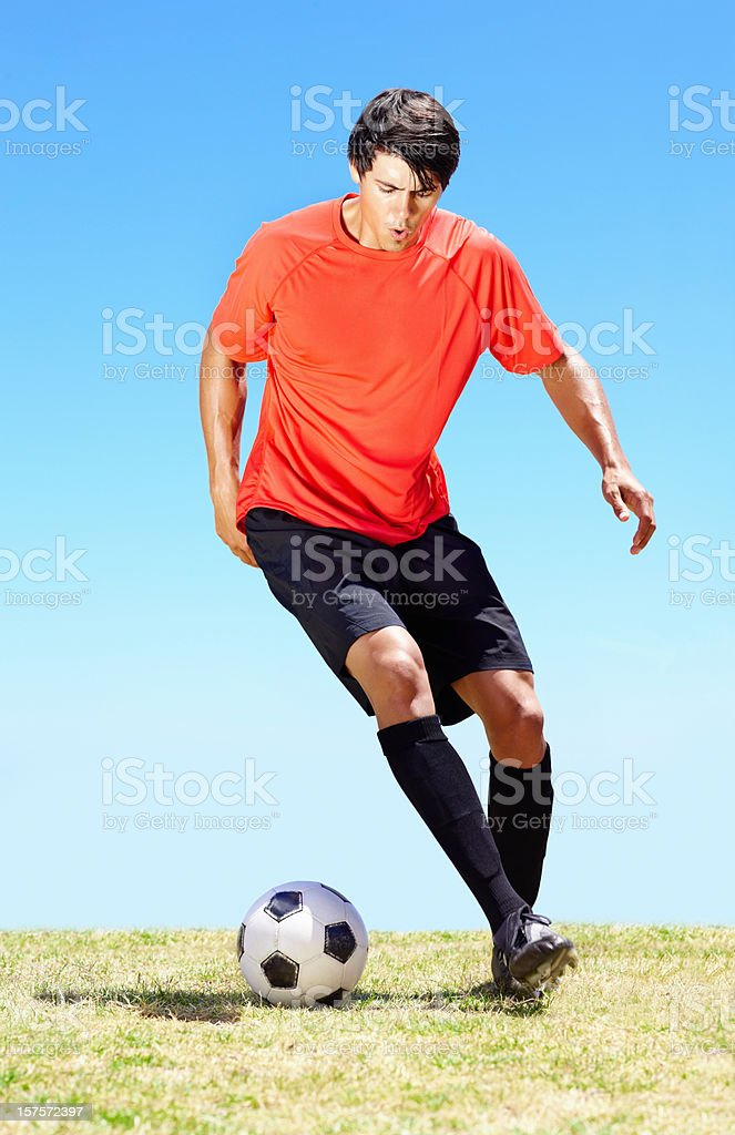 Young footballer dribbling a ball while on the field royalty-free stock photo