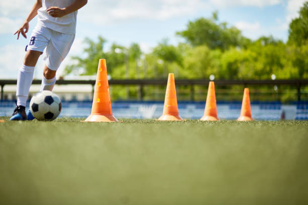 Young Footballer Enjoying Practice Low section portrait of unrecognizable boy running in football field leading ball between row of orange cones during practice practicing stock pictures, royalty-free photos & images