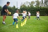Fit male coach in early 40s guiding young boy and girl Spanish footballers through practice drills around yellow traffic cones.