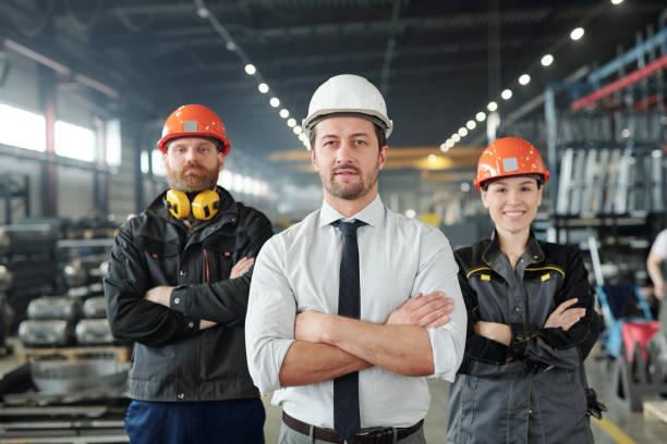 Junger Vorarbeiter in Formalwear und Hardhat und seine beiden Untergebenen – Foto