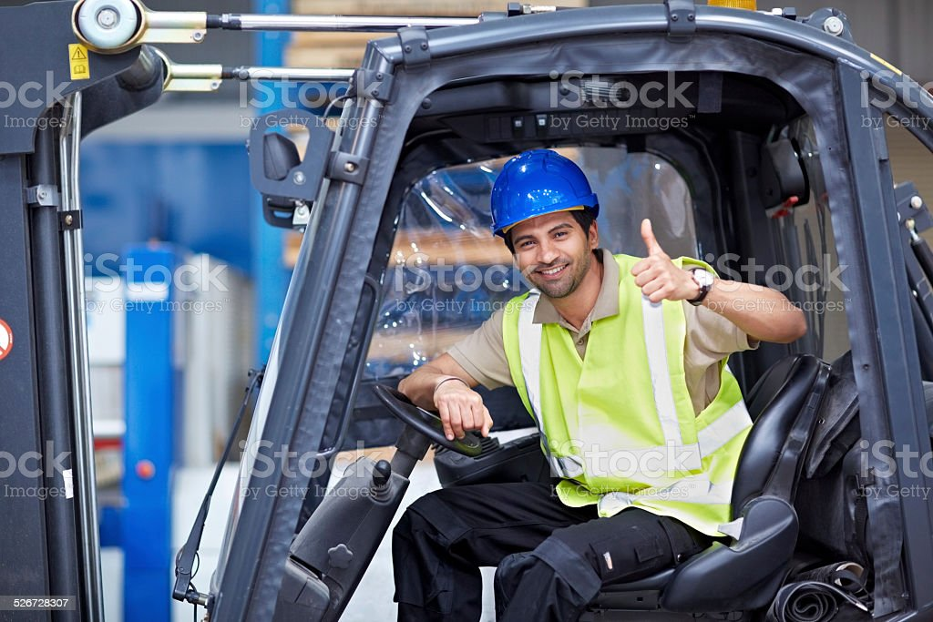 Young forklift driver giving thumbs up stock photo
