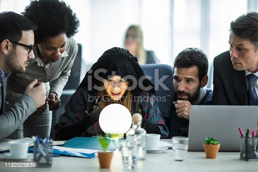Female fortune teller analyzing crystal ball while predicting the future of business people.