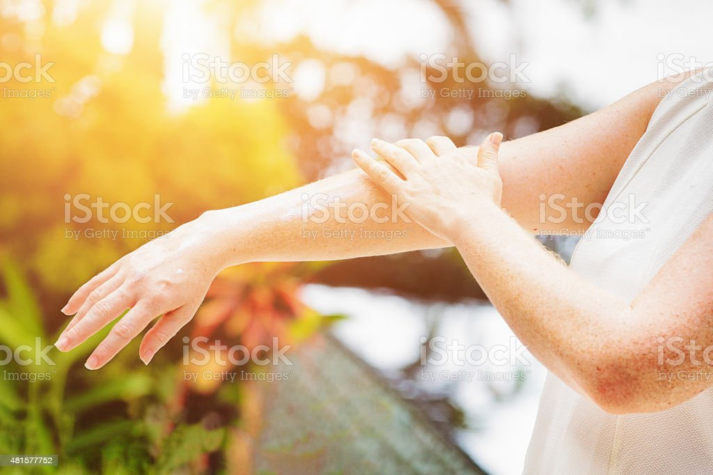 Young freckled woman applying sun screen cream on her arms stock photo