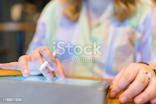 A young freelance body positive female illustrator is drawing an illustration on a digital tablet with a digital pen in a cafe.