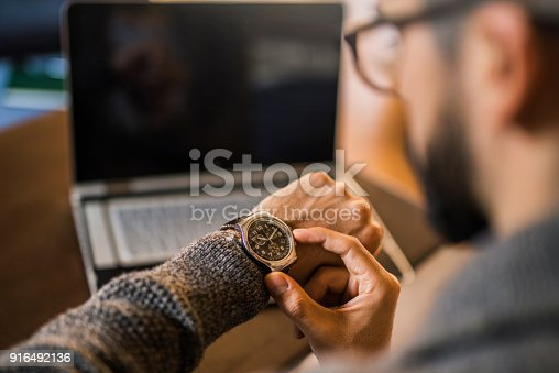 Young freelancer checking time while working.