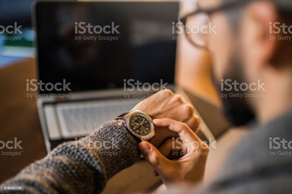 Young freelancer checking time while working. stock photo