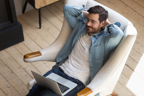 Young freelancer relaxing on armchair, taking break during remote workday. stock photo