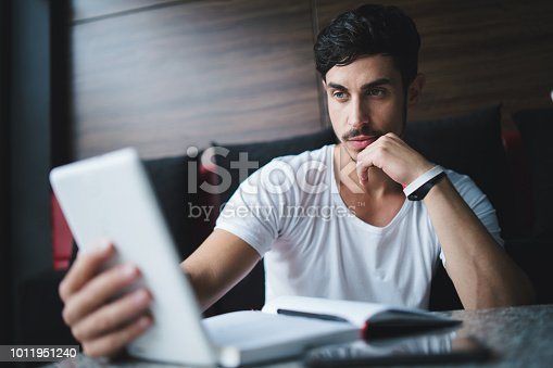 1175668510 istock photo Young freelancer researching new ideas at cafe 1011951240