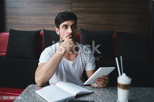 1175668510 istock photo Young freelancer researching new ideas at cafe 1011951248