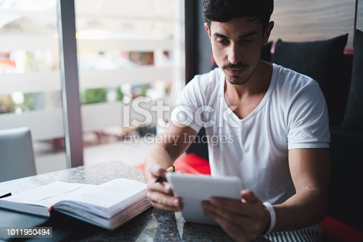 1175668510 istock photo Young freelancer taking notes at cafe 1011950494
