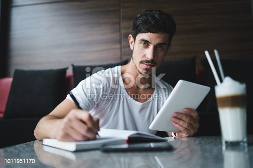 1175668510 istock photo Young freelancer taking notes at cafe 1011951170