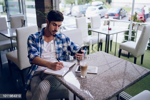 1175668510 istock photo Young freelancer taking notes at cafe 1011954310