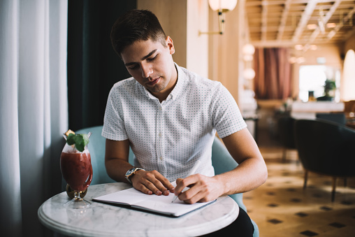 Young freelancer writing in notebook while sitting at cafe
