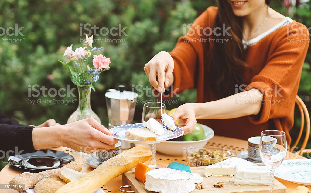 Young French couple eating in the garden home stock photo