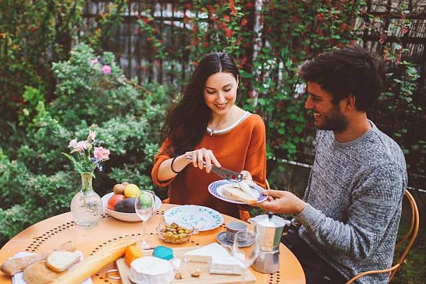 francés pareja joven teniendo un brunch dominical en el jardín - couple lunch outdoors fotografías e imágenes de stock