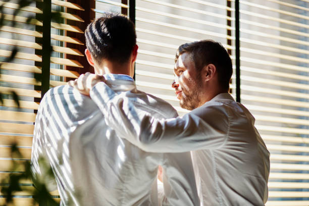 Young friendly businessmen standing near window Back view of two young elegant men on business meeting standing near window in embrace and chatting consoling stock pictures, royalty-free photos & images
