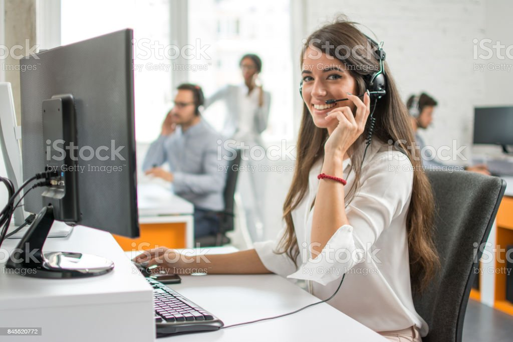 Young friendly operator woman agent with headsets working in a call centre. - foto stock