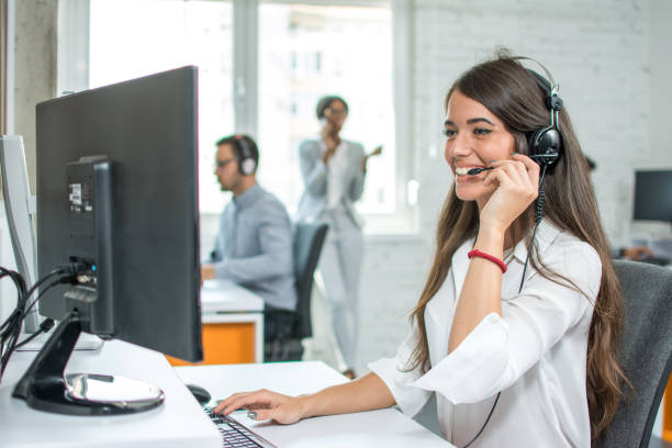 Young friendly operator woman agent with headsets working in a call centre. stock photo