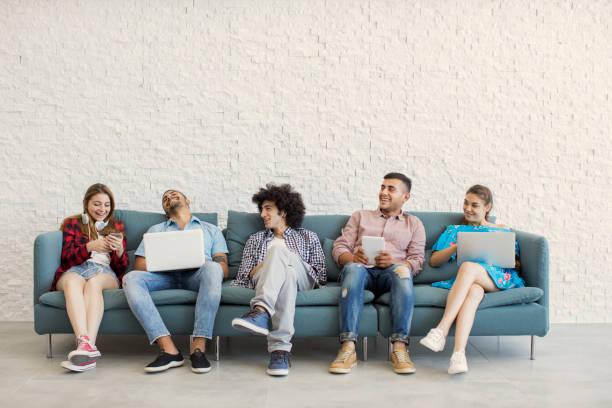 young friends and technology concept - sitting laptop стоковые фото и изображения