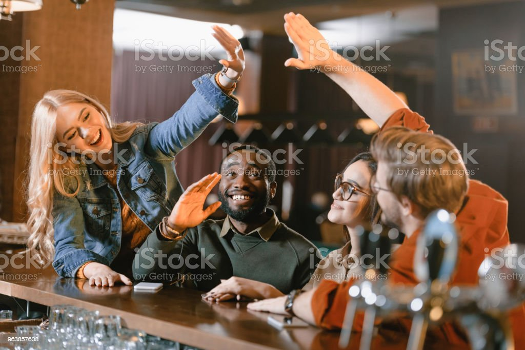 young friends at bar giving high five to each other - Royalty-free Adult Stock Photo