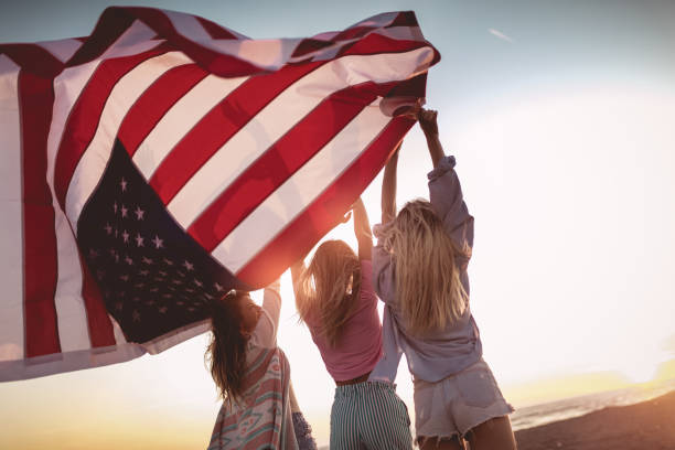 Young friends carrying american flag on the beach stock photo