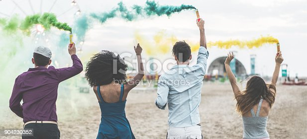 istock Young friends celebrating at party festival with smoke bombs on the beach - Happy people having fun in summer vacation - Friendship, youth lifestyle and fest concept - Main focus on center guys 904230352