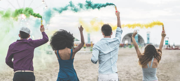 young friends celebrating at party festival with smoke bombs on the beach - happy people having fun in summer vacation - friendship, youth lifestyle and fest concept - main focus on center guys - atmosfera wydarzenia zdjęcia i obrazy z banku zdjęć