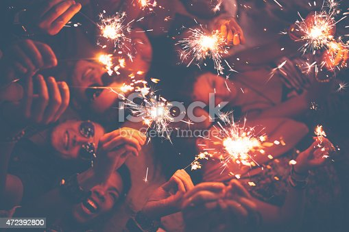 471113366istockphoto Young friends celebrating with sparklers at a beachparty 472392800