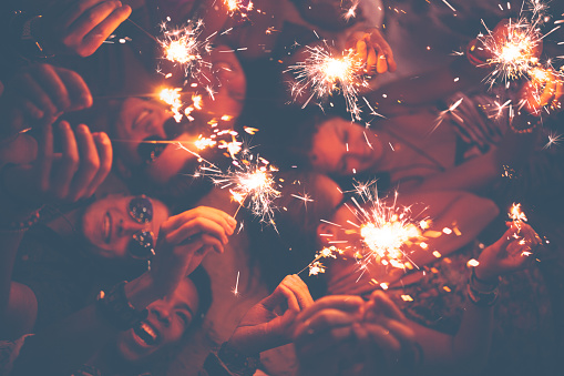 471113366 istock photo Young friends celebrating with sparklers at a beachparty 472392800