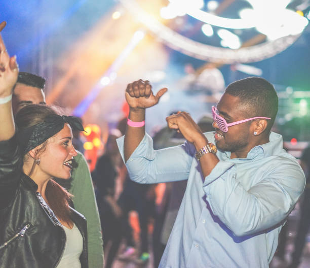 Young friends dancing at party in night club - Diverse culture people enjoying weekend nightlife with original laser lights colors in background - Youth concept - Soft focus on black man - Warm filter stock photo