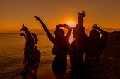 Young friends dancing on the beach at sunset
